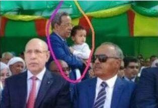 صورة للمستشار وهو يحمل حفيد الرئيس في موضع مذل ومهين