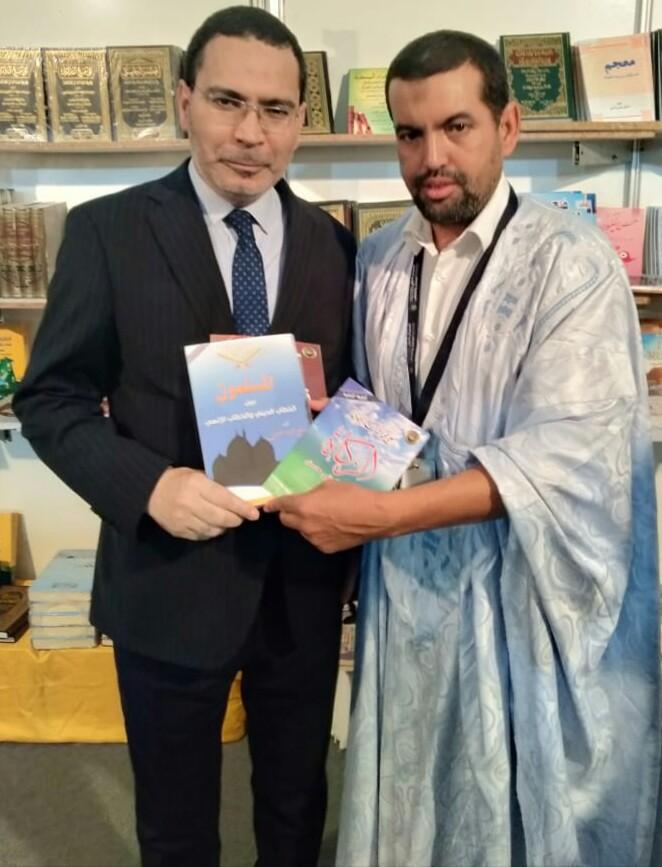الناطق الرسمي باسم الحكومة المغربية وهو يتسلم  كتب علي محمد الشرفاء المحمادى