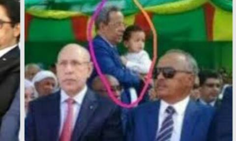 صورة للمستشار المشؤوم وهو يحمل حفيد الرئيس في موضع مذل ومهين
